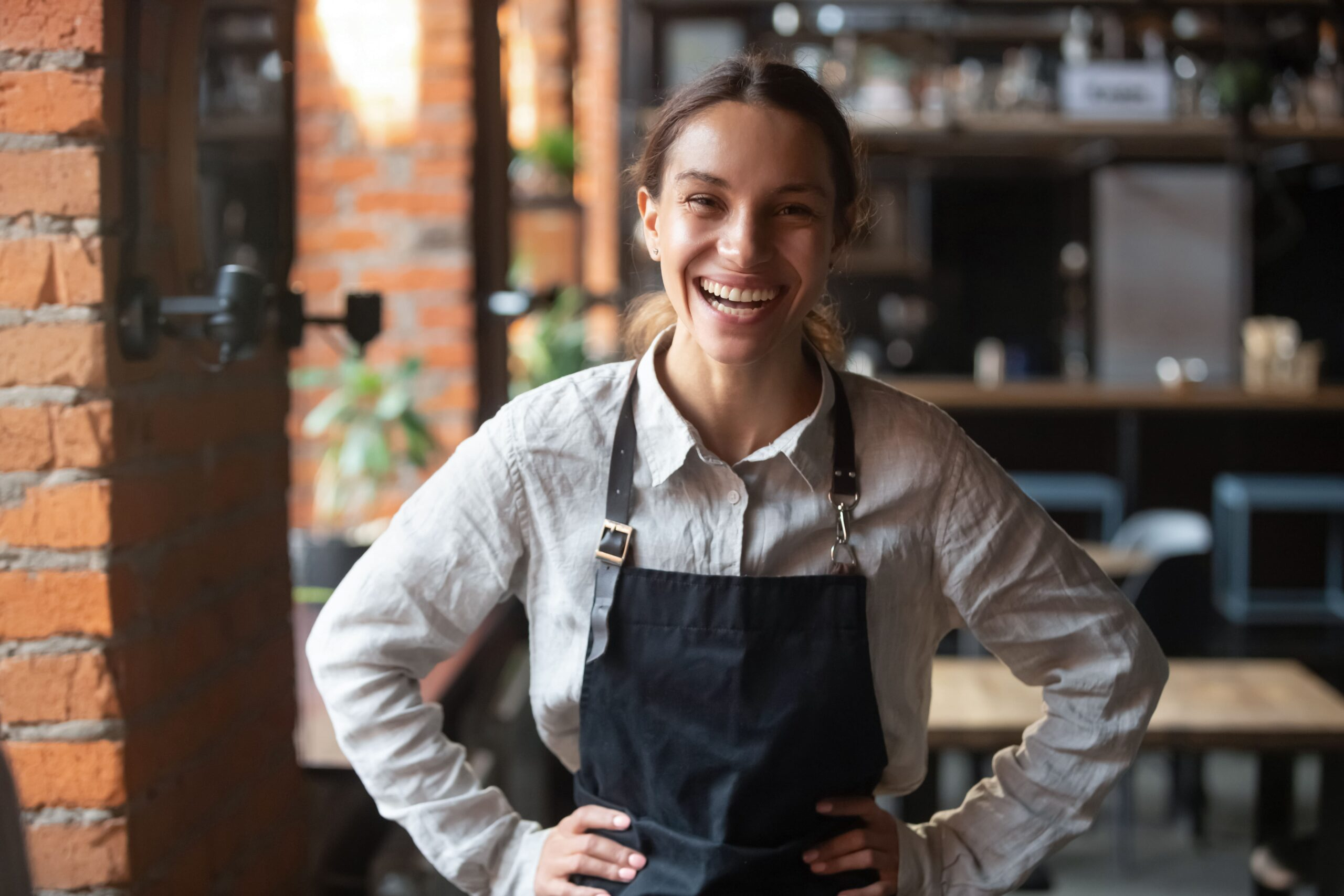A small business owner with an apron on smiling