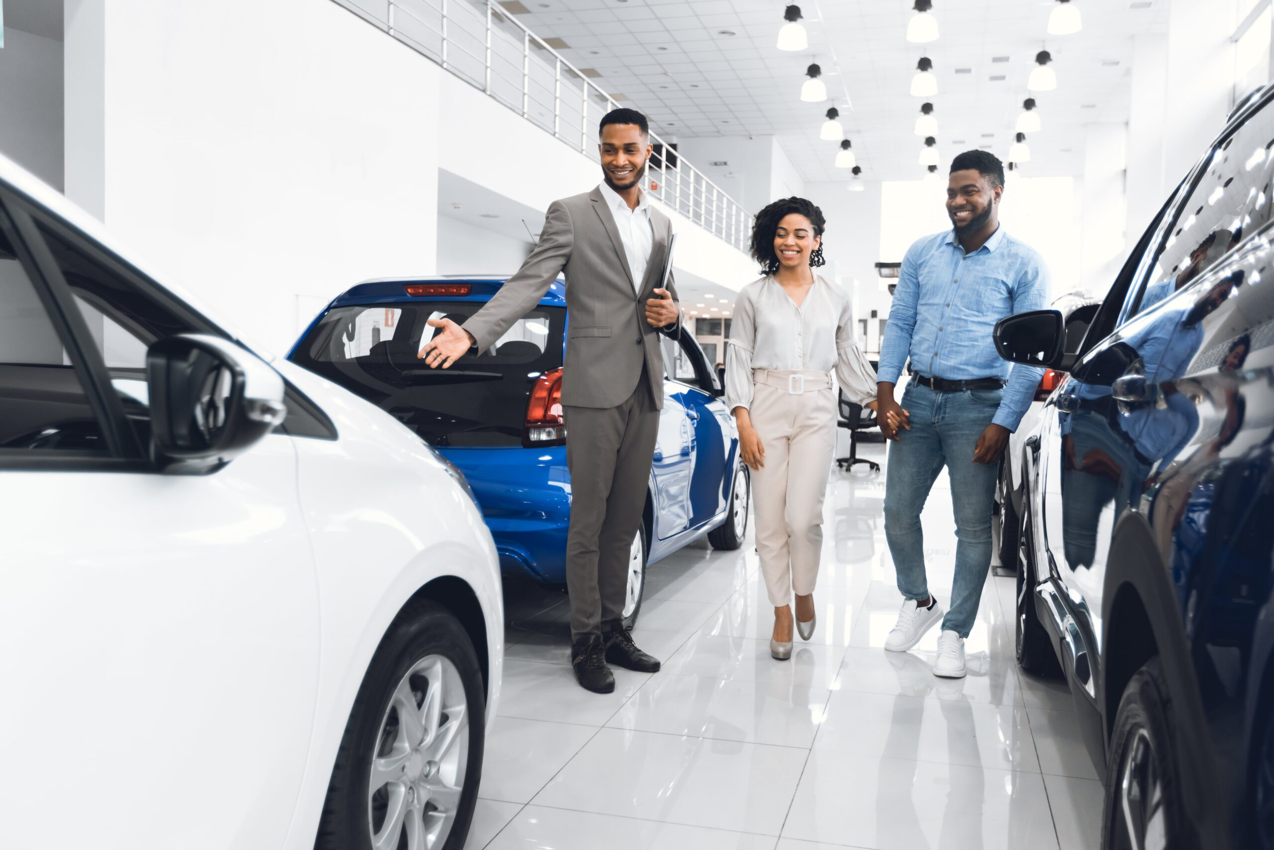 two people looking at cars that are being presented by a salesman